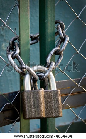 padlock suspended by two chains - stock photo