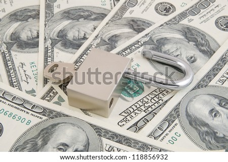 Padlock with key on dollars background
