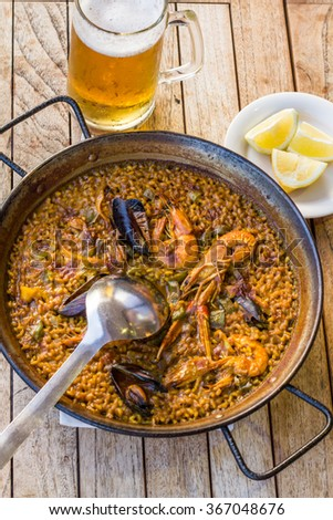 Paella in Barcelona Paella with seafood with lemon wedges and a glass of beer on a wooden table - stock photo