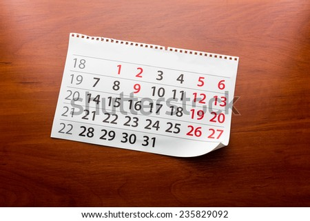 Page from calendar lies on the table - stock photo