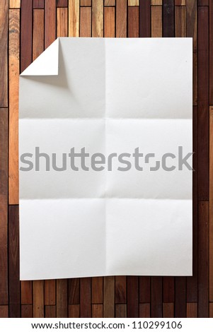 page of White paper folded and wrinkled on wood background with shadow - stock photo
