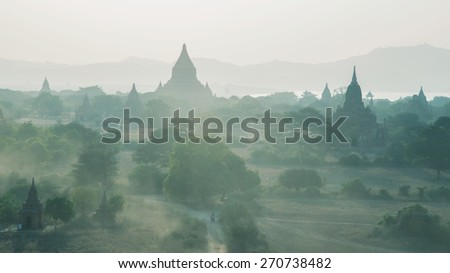 Pagodas in Burma. Old Bagan has thousands of Buddhist temple ruins of considerable historic significance. Ideal destination for tourists and travelers to Myanmar. Dust flies near sundown.  - stock photo