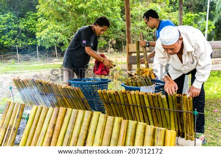 "PAHANG, M'SIA-JULY 27: Unidentified Malaysian traditional food seller was cooking ""lemang"" at Kuantan town on July 27, 2014 in Pahang, Malaysia. Muslims around the world celebrate Aidilfitri tomorrow - stock photo"