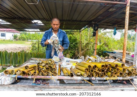 "PAHANG, M'SIA-JULY 27: Unidentified Malaysian traditional food seller was packing ""lemang"" at Kuantan town on July 27, 2014 in Pahang, Malaysia. Muslims around the world celebrate Aidilfitri tomorrow - stock photo"