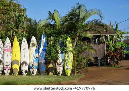 PAIA, HI -30 MARCH 2016: Colorful surfboards are lined up in the streets of Maui. Hawaii is the birthplace of modern surfing and home to the world's major big wave surfing competitions. - stock photo