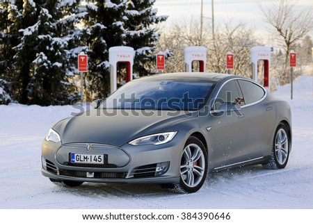 PAIMIO, FINLAND - JANUARY 17, 2016: Unidentified man drives Tesla Model S at Supercharger Station Paimio on a cold wintery day. Unlike conventional cars, electric cars will always start in winter. - stock photo