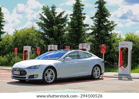PAIMIO, FINLAND - JULY 5, 2015: Tesla Model S is being charged at Tesla Supercharger station. Charging the battery from 10 to 80 percent takes about 40 minutes.   - stock photo