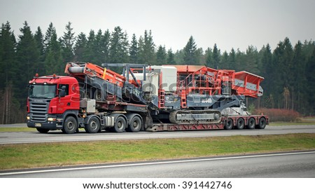 PAIMIO, FINLAND - NOVEMBER 1, 2015: Scania R620 Semi hauls Sandvik US440i Mobile Cone Crusher. The heavy duty cone crusher is designed for the needs of large mine or quarry operators. - stock photo