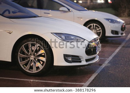 PAIMIO, FINLAND - NOVEMBER 14, 2015: Two white Tesla Model S cars are being charged at Tesla Supercharger station at night. Tesla Supercharging are open at any time. - stock photo