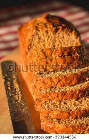 Pain d epices or French Honey Bread Loaf. Sliced on Wooden Board with Knife. Original Homemade Fresh Baked. Country, Still Life. Close up, Selective. - stock photo