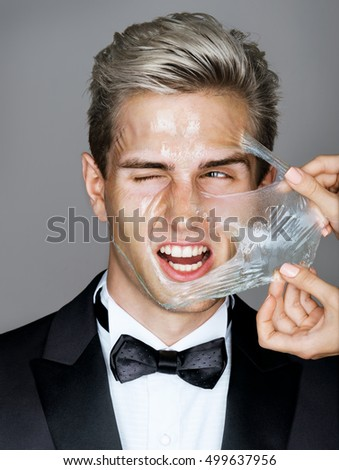 Pain. Elegant man in black suit removes peeling off a facial mask. Photo disaffected rich man on gray background. Skin care concept