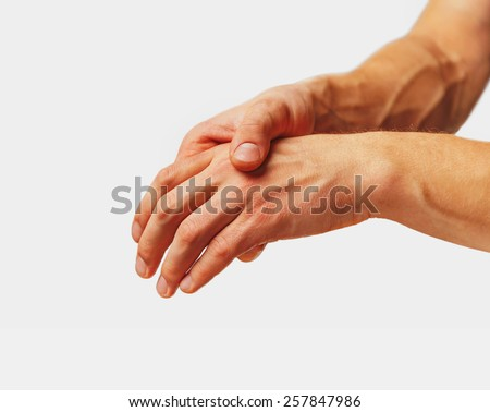 Pain in a male hand. Man holds his hand. - stock photo