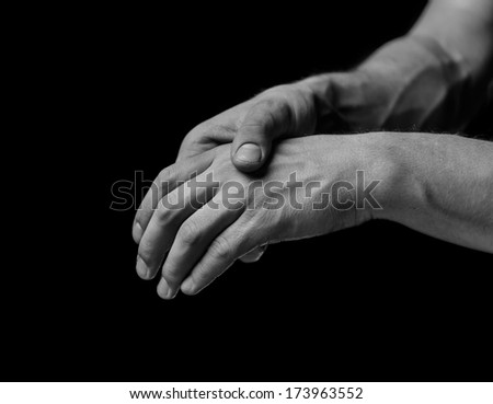 Pain in a male hand. Man holds his hand, black and white image