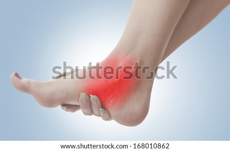 Pain in a woman ankle. Female holding hand to spot of ankle-ache. Concept photo with Color Enhanced blue skin with read spot indicating location of the pain.