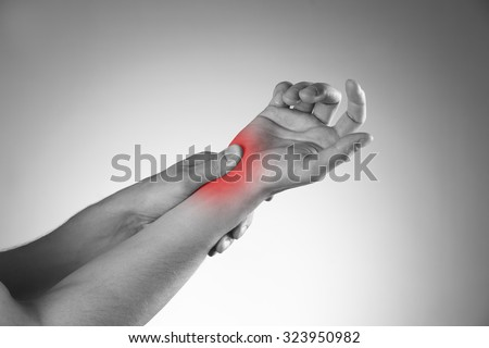 Pain in the joints of the hands. Carpal tunnel syndrome. Black and white photo with red dot - stock photo