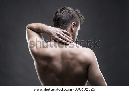 Pain in the neck. Man with backache. Muscular male body. Handsome bodybuilder posing on gray background. Low key close up studio shot. Middle part of the body - stock photo