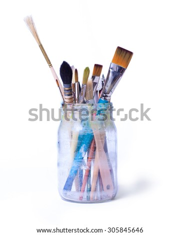 Paint art brushes in a glass jar isolated over white background. - stock photo