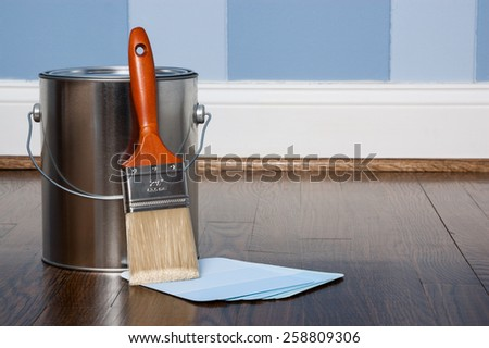 Paint brush, chips and can in a bedroom with blue two toned painted walls on a hardwood floor - stock photo