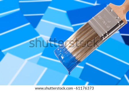 Paint brush loaded with blue paint with colour swatches below - stock photo