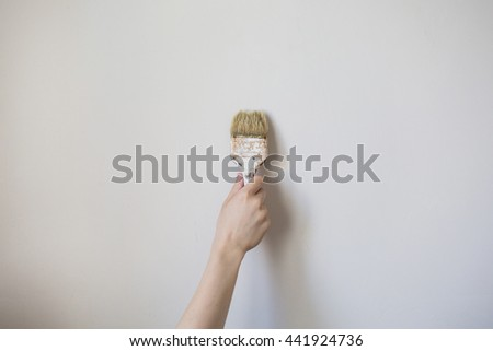 Paint brush with a wooden handle in a man's hand on a light background. Home repairs . Concept. The tool for painting of walls. Dirty brush in gray wall - stock photo