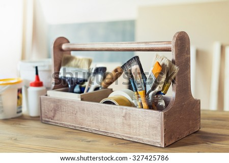 Paint brushes and supplies in wooden toolbox - stock photo