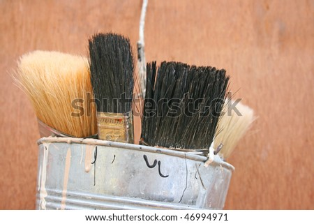 Paint brushes in painters kettle.