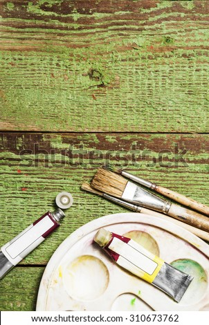 Paint brushes set and a palette with oil paint tubes on a green wooden background - stock photo