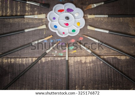 Paint brushes set and a palette with oil paint tubes on wooden background - stock photo