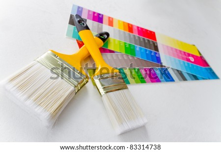 Paint brushes with color guide - isolated over white - stock photo