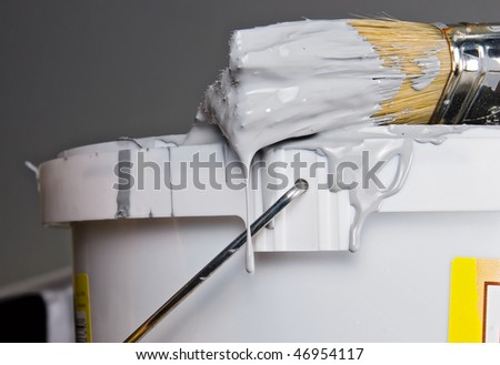 Paint bucket and paintbrush over gray wall - stock photo