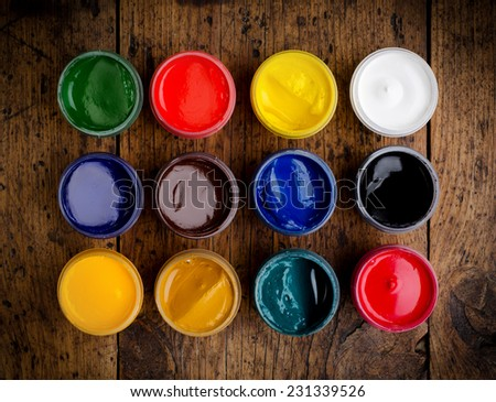 paint buckets on wood background - stock photo