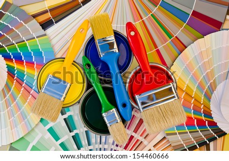 Paint cans and brushes on stripes of color swatches. Sample of colorful paint. Cans of red, yellow, blue and green paint. - stock photo