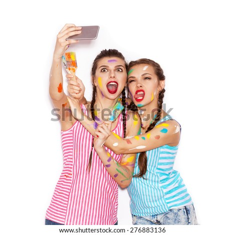 Paint on the face of pretty girl friends having fun. Women with paintbrush  Taking Self Portrait with Their Phone. White background not isolated - stock photo