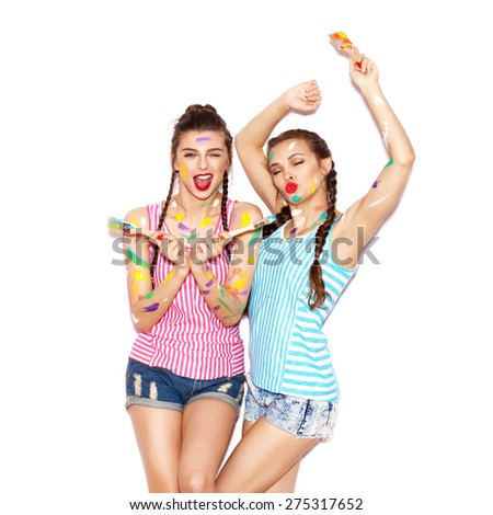 Paint on the face of pretty girl friends having fun. Women with paintbrush. White background not isolated - stock photo