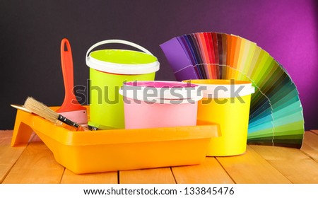 Paint pots, paintbrushes and coloured swatches on wooden table on dark purple background - stock photo