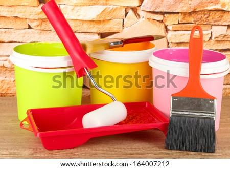 Paint pots, paintbrushes and coloured swatches on wooden table on stone wall background - stock photo