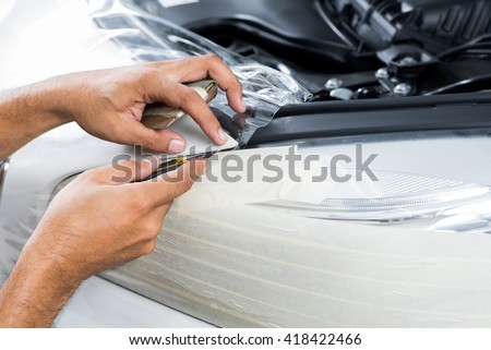 Paint protection film series : Cutting paint protection film on white car - stock photo