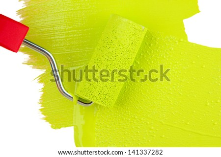 Paint roller brush with green paint, on wooden background - stock photo