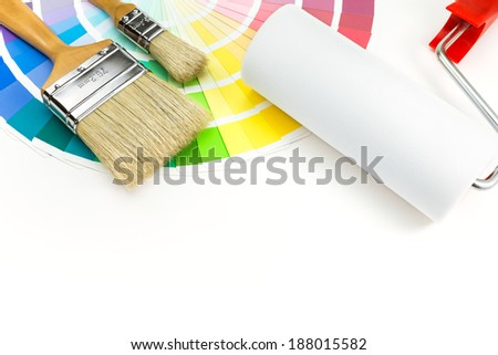 Paint roller, brushes and color sample catalog on white background