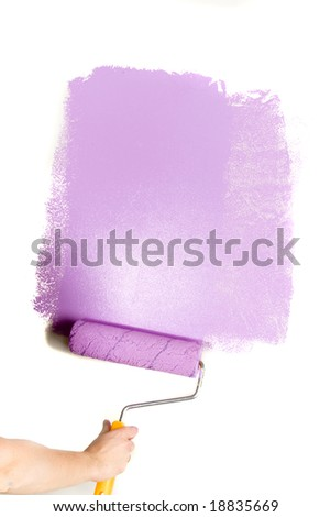 Paint roller in hand. Painting the wall. - stock photo