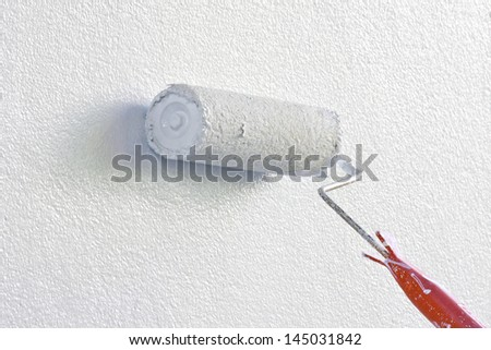 Paint Roller on White Wall - stock photo