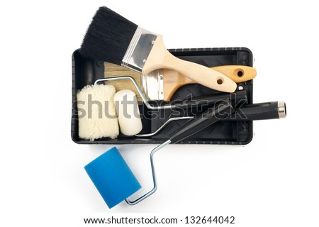 Paint rollers and brush on black tray - stock photo