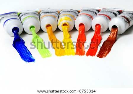 Paint tubes with different colors spread over a white surface - stock photo