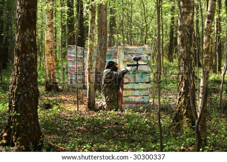 Paintball gamer, solder attacking from knee position from behind cover - stock photo