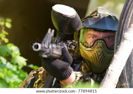 paintball sport player in protective uniform and mask aiming gun before shooting under cover in forest