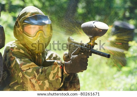 paintball sport player wearing protective mask aiming gun and shotted down with paint splash in summer - stock photo