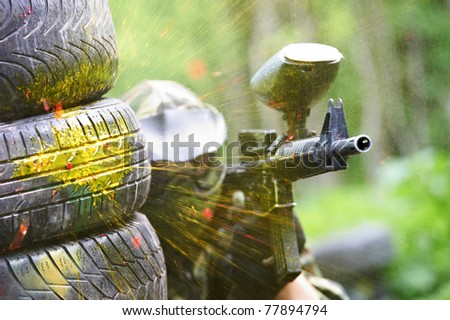 paintball sport player wearing protective mask aiming gun from shelter under gunfire attack with paint splash - stock photo