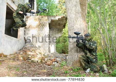 paintball sport players during tactical training game attack in forest with protective uniform and masks - stock photo