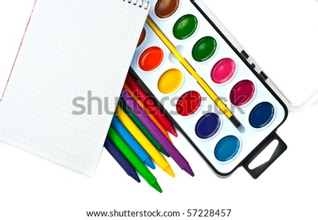 Paintbox, crayons and note book on white - stock photo