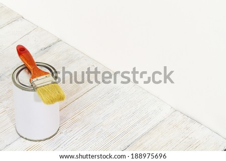 Paintbrush and can, paint brush and white color container on wooden floor background  - stock photo